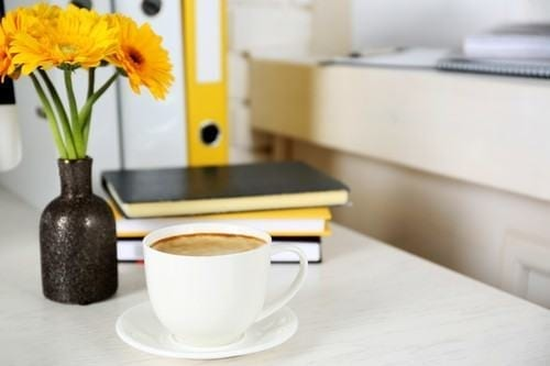 Cup of coffee and flowers on workplace in home or office